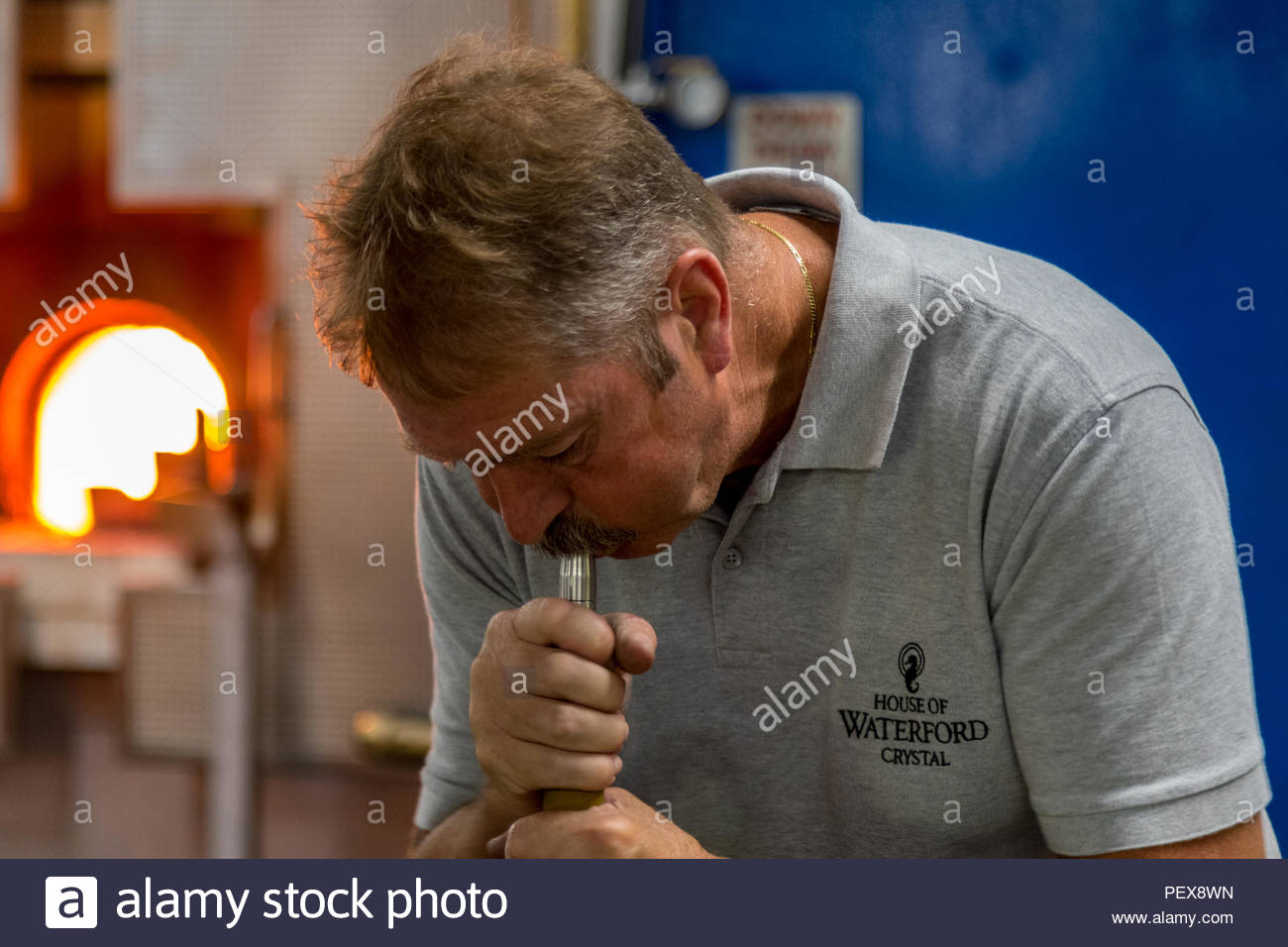 Workers in the Waterford Crystal factory in the Republic of Ireland. A workman blows a block of gathered block of molten glass into a mould - Stock Image