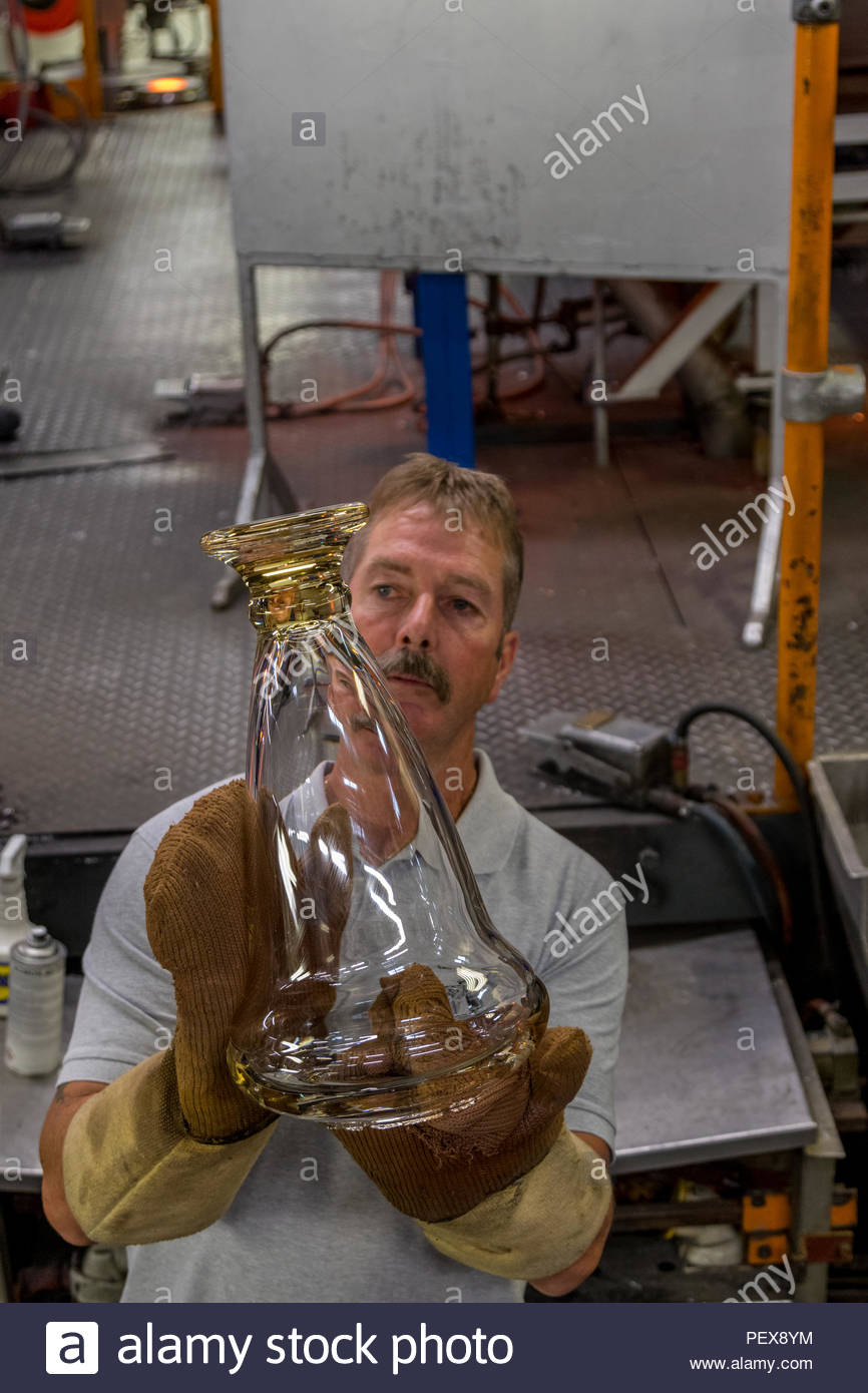 Workers in the Waterford Crystal factory in the Republic of Ireland. A workman inspects a vase before placing it into an oven to cool. - Stock Image