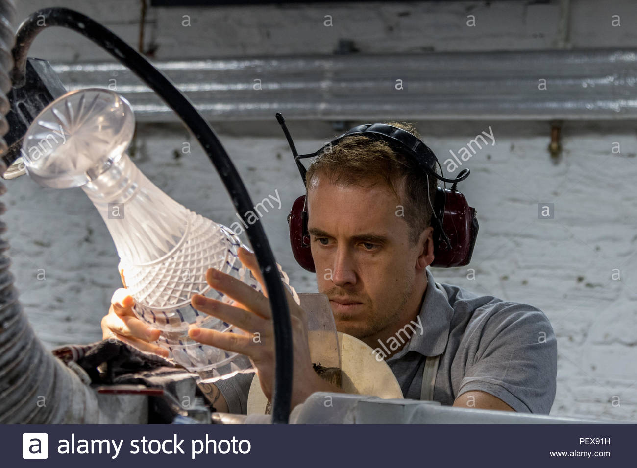 Workers in the Waterford Crystal factory in the Republic of Ireland.  A skilled engraver puts the finishing touches to a cut glass vase - Stock Image