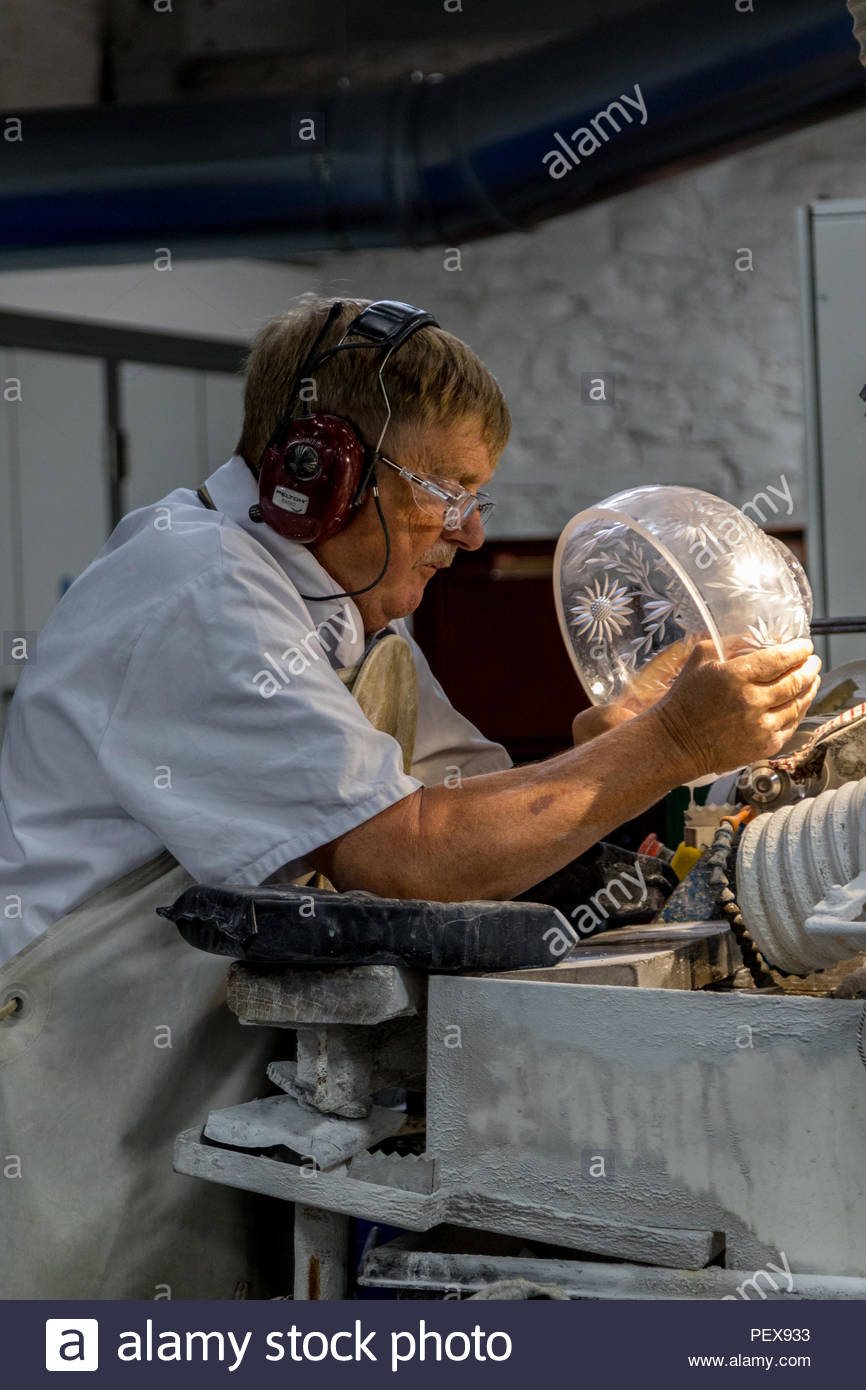 Workers in the Waterford Crystal factory in the Republic of Ireland. A skilled engraver puts the finishing touches to a cut glass bowl. - Stock Image