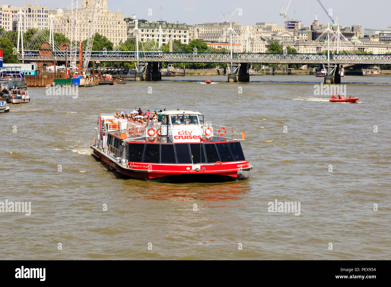 Sightseeing cruise ship, City Cruises on the River Thames with Jubilee and Hungerford bridge in the background.London, England Stock Photo