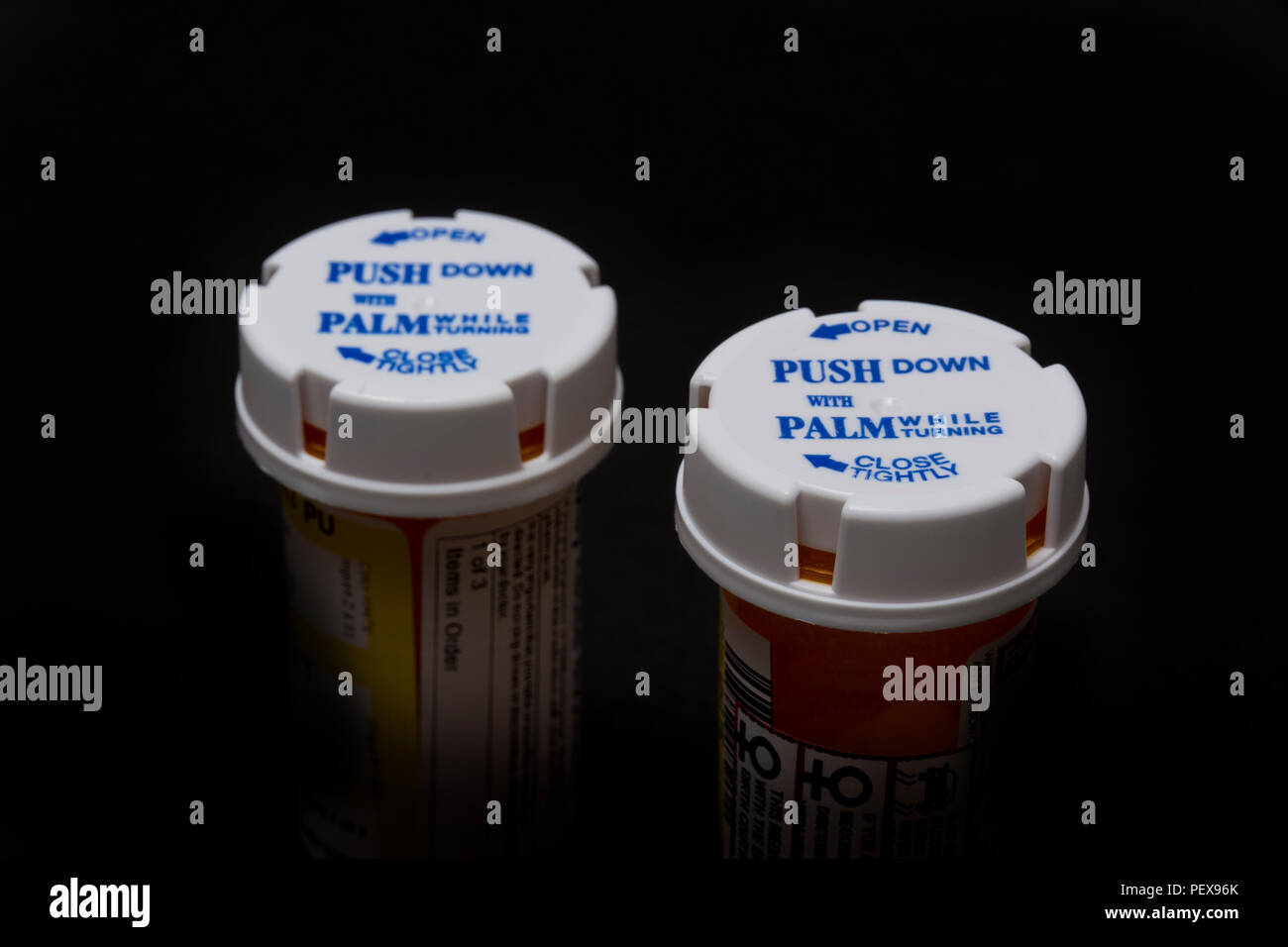 A pair of prescription bottles with child-proof caps. - Stock Image