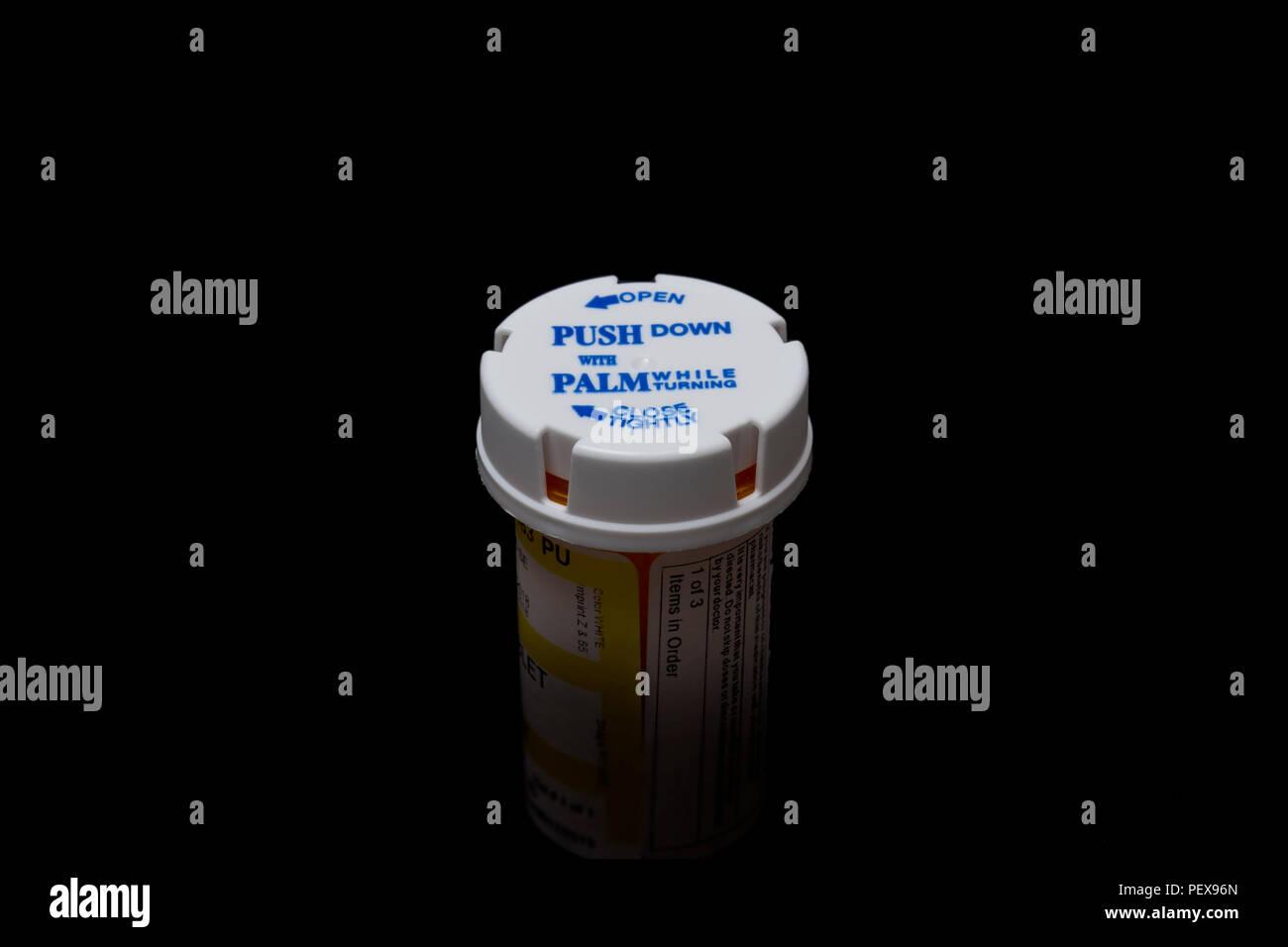 A prescription bottle with a child-proof cap. - Stock Image
