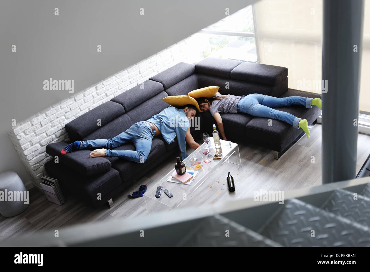 Drunk Friends Sleeping On Sofa In Messy Room After Party - Stock Image