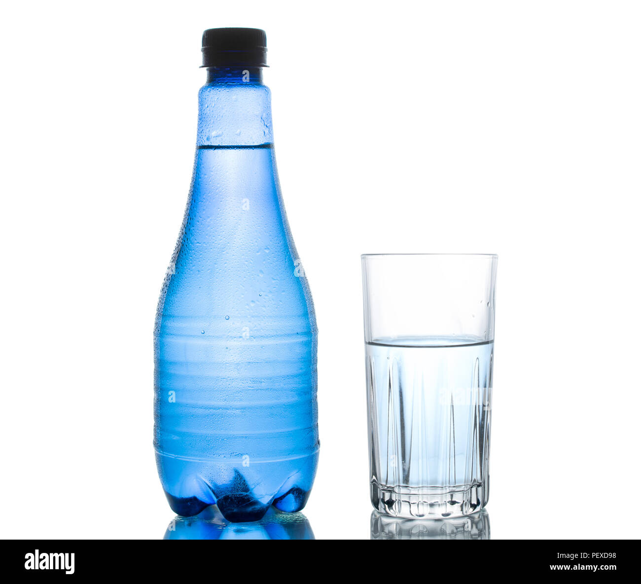 Blue water bottle isolated on white background with small water droplets and a clear drinking glass - Stock Image