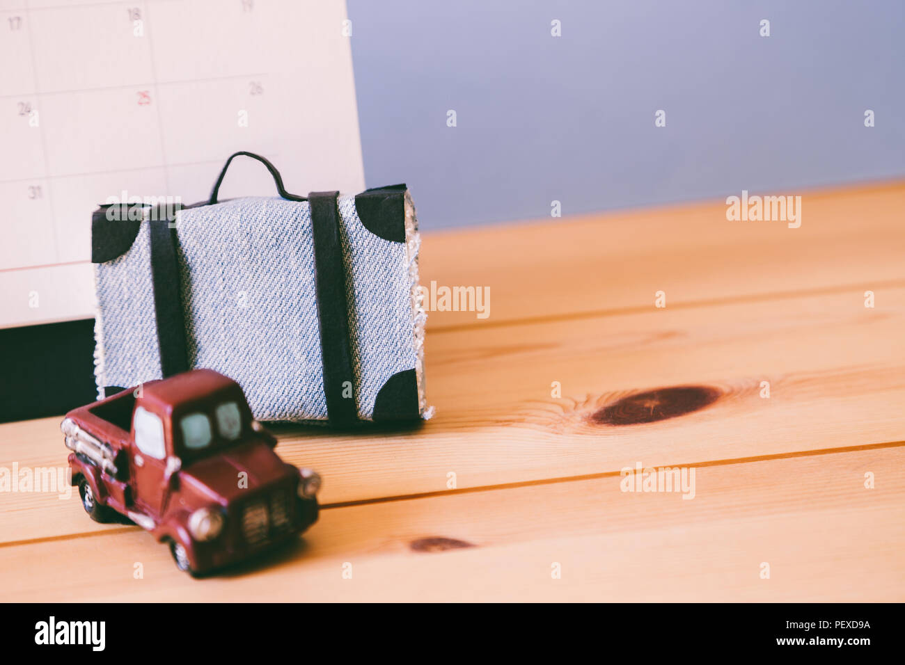 Travel suitcase, car and calendar on table, Summer vacation schedule concept - Stock Image