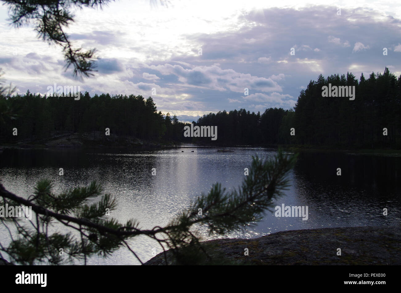 Dark clouds are forming over a calm lake in Dalarna in Sweden - Stock Image