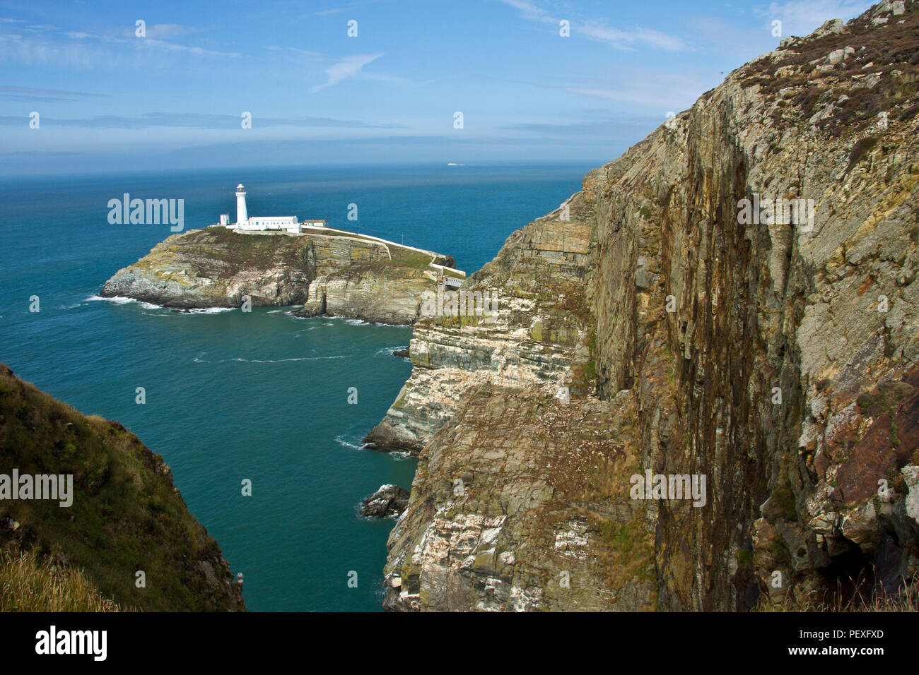 The rugged cliffs and shoreline of north Anglesey have been a potential danger to shipping for millenia and the South Stack Lighthouse - Stock Image