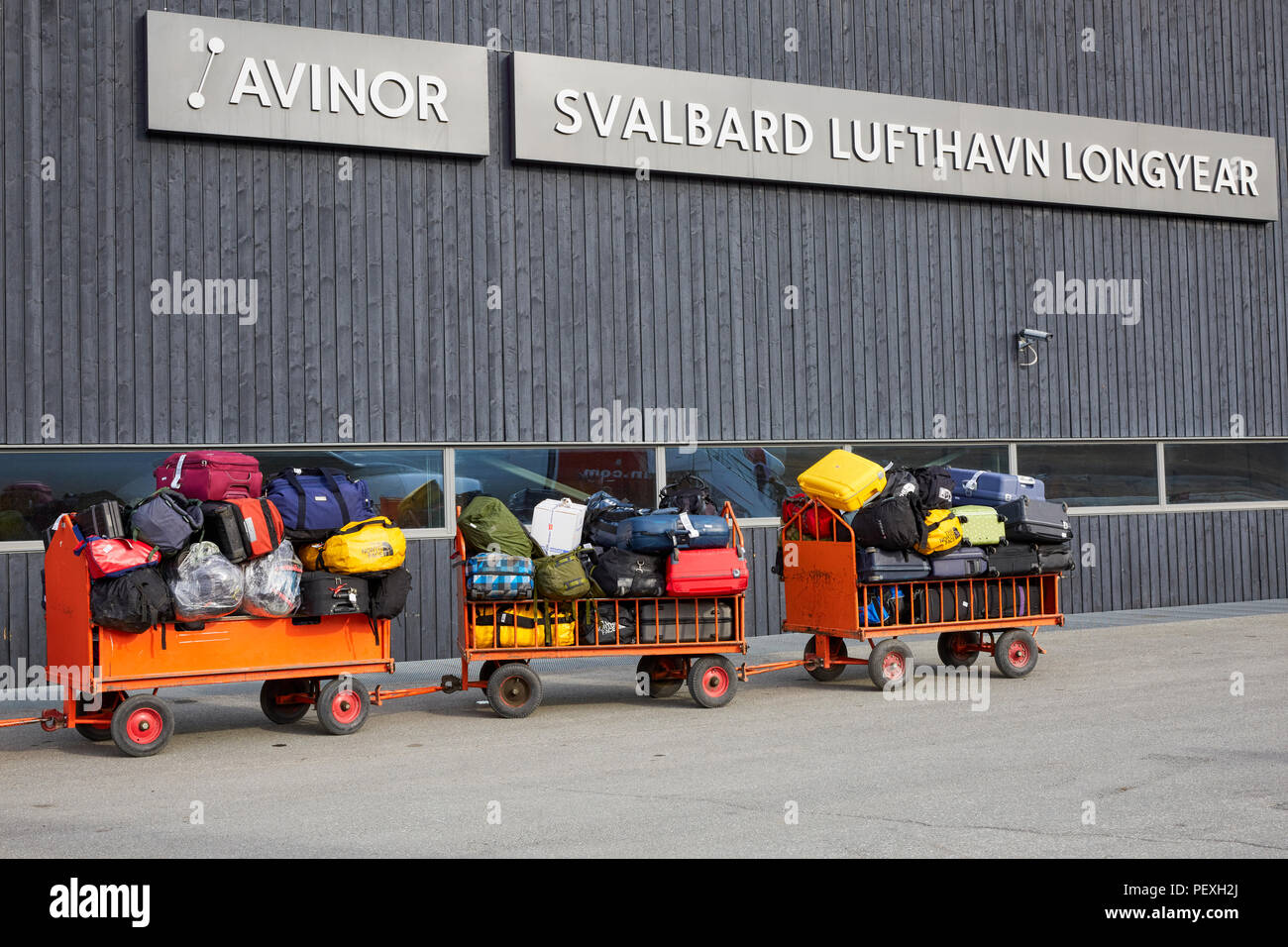 Baggage carts are waiting to be loaded or unloaded at Svalbard Longyearbyen Airport Longyearbyen Lufthavn - Stock Image