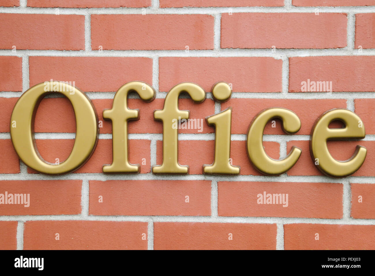 Letters Spelling OFFICE Sign In Gold On A Brick Wall
