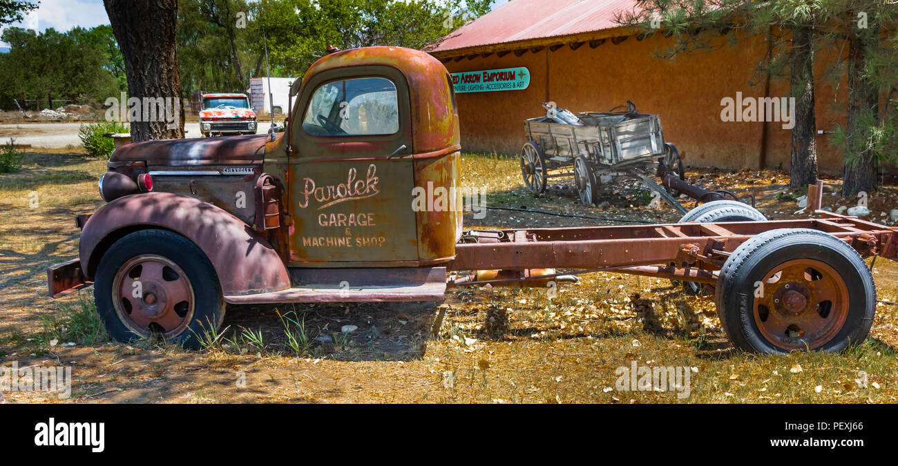 TAOS, NM, USA-8 JULY 18: Two old trucks and  a farm wagon, setting outside the Red Arrow Emporium. - Stock Image