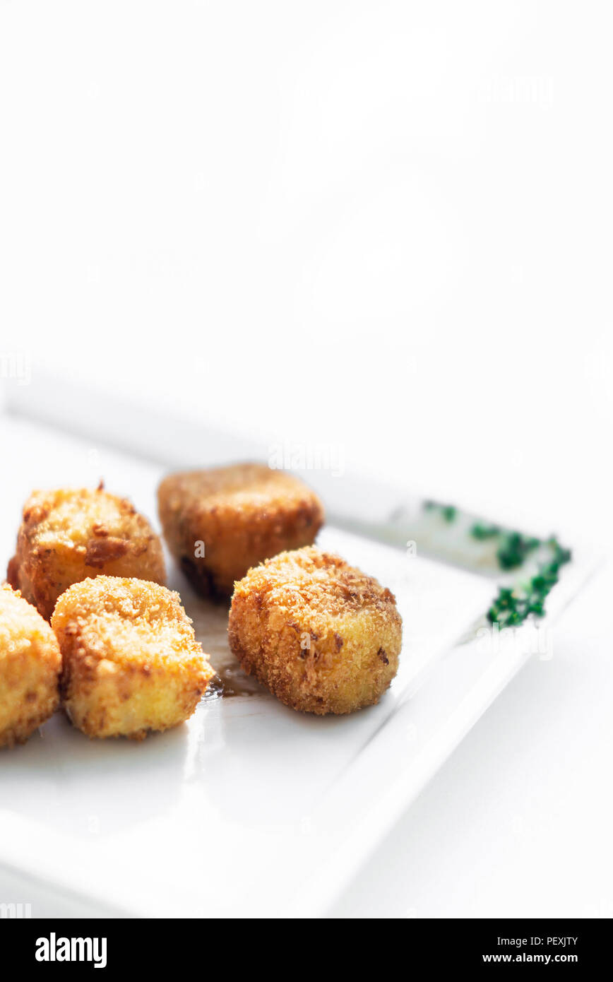 fried mashed potato square croquettes simple vegetarian side dish on white plate - Stock Image