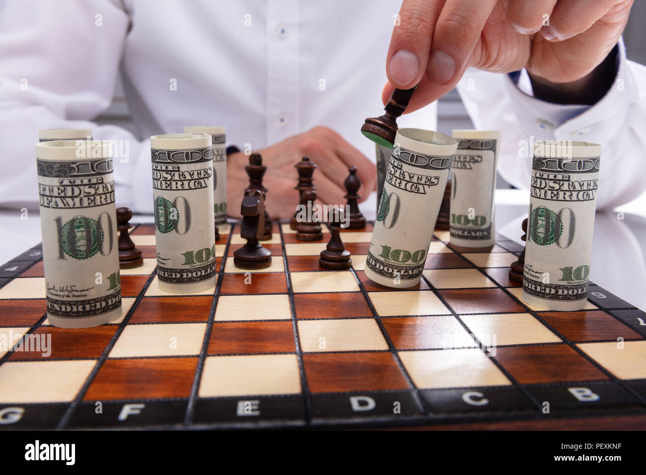 Close-up Of A Person Falling Rolled Up Banknote With Chess Piece Stock Photo