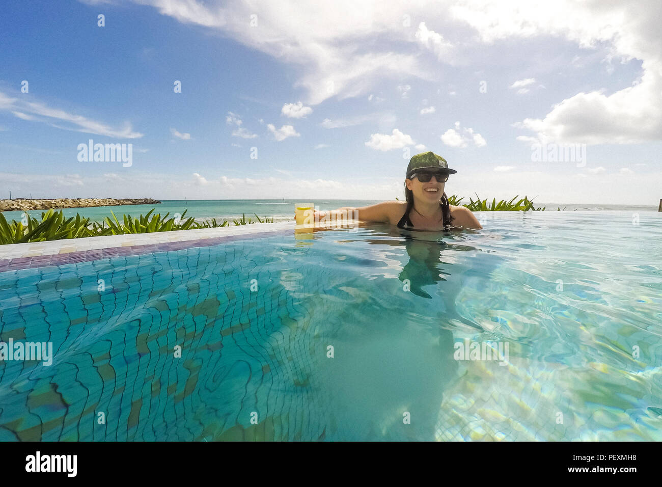 Woman swimming in oceanside swimming pool with cocktail - Stock Image