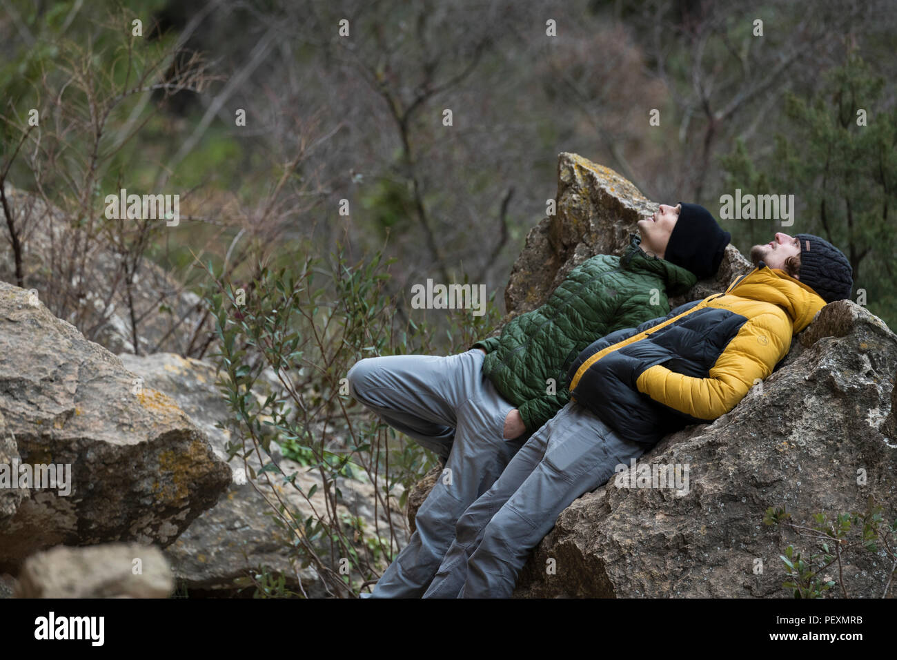 Two men lying against rock and looking up - Stock Image
