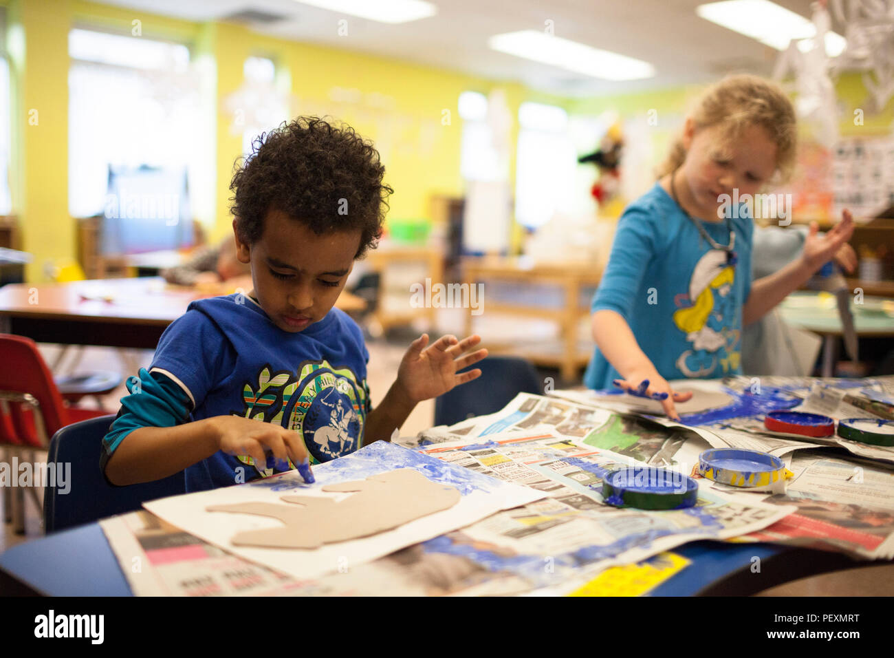 Schoolchildren finger painting in classroom - Stock Image