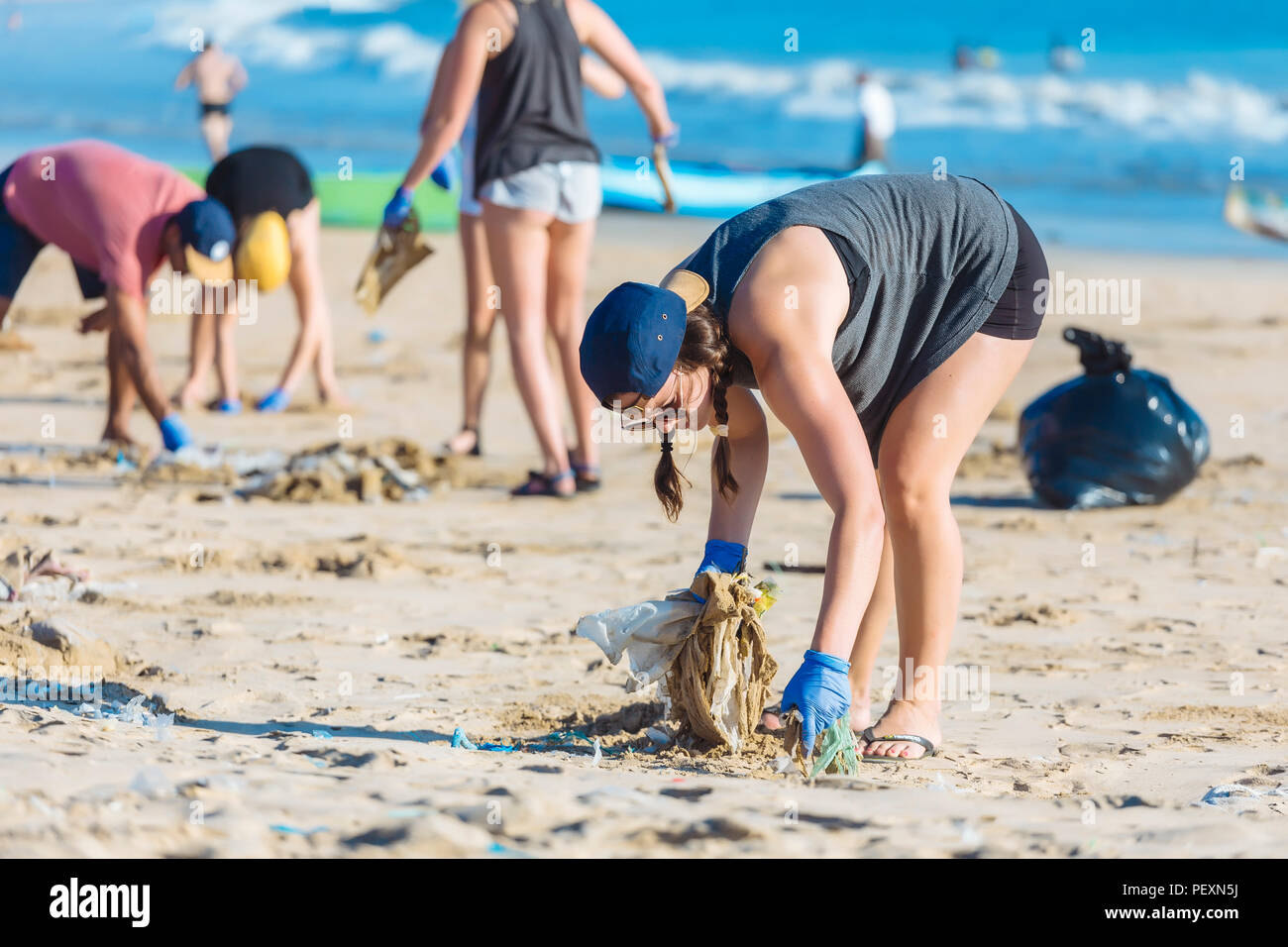 Woman picking up trash at beach, Jimbaran, Bali, Indonesia - Stock Image