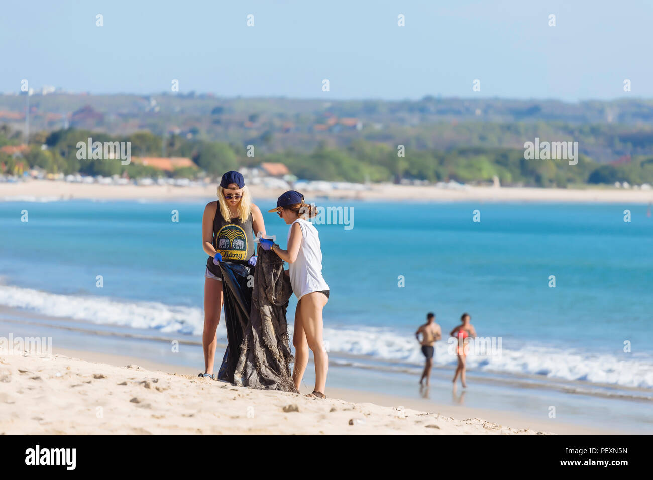 Women picking up trash at beach, Jimbaran, Bali, Indonesia - Stock Image