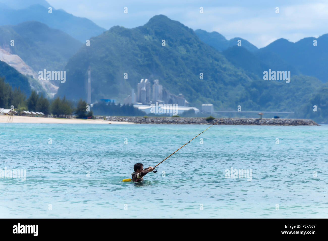 Fisherman in sea with fishing rod, Banda Aceh, Sumatra, Indonesia - Stock Image