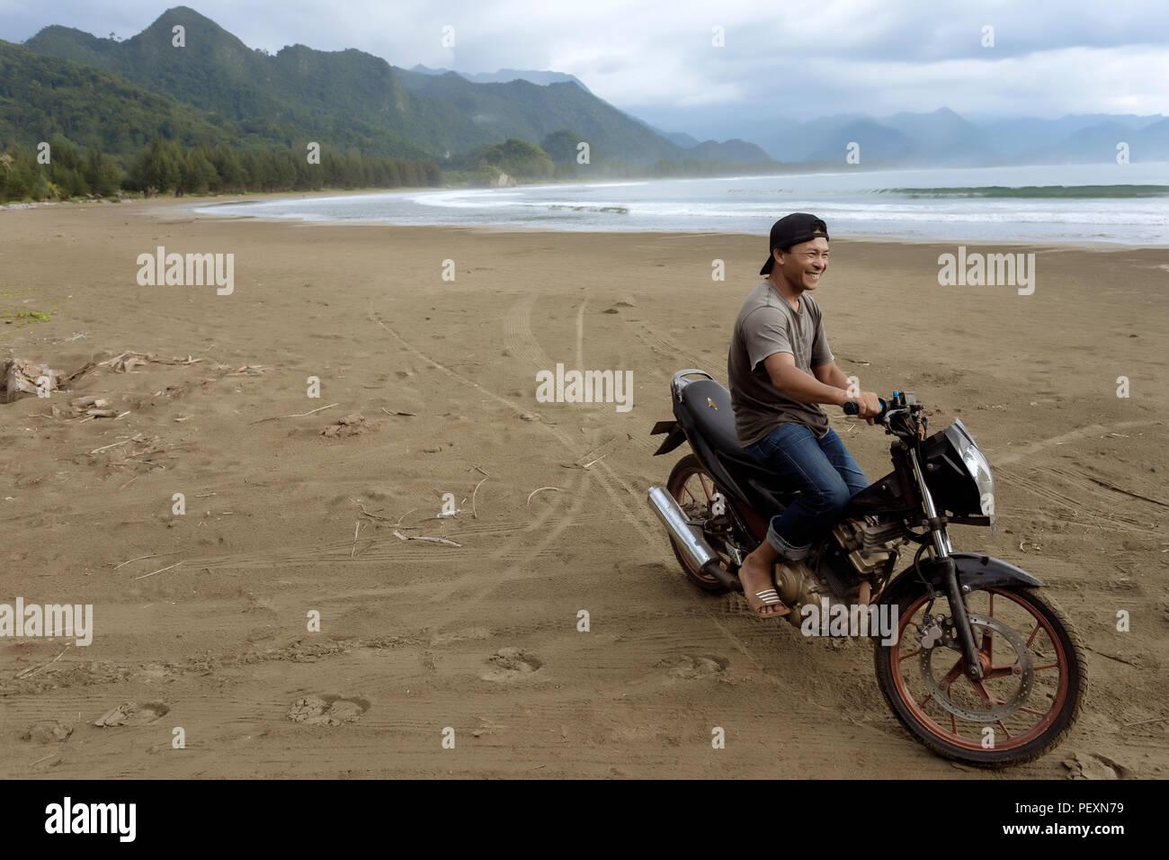 Asian man on motorcycle on beach, Banda Aceh, Sumatra, Indonesia - Stock Image