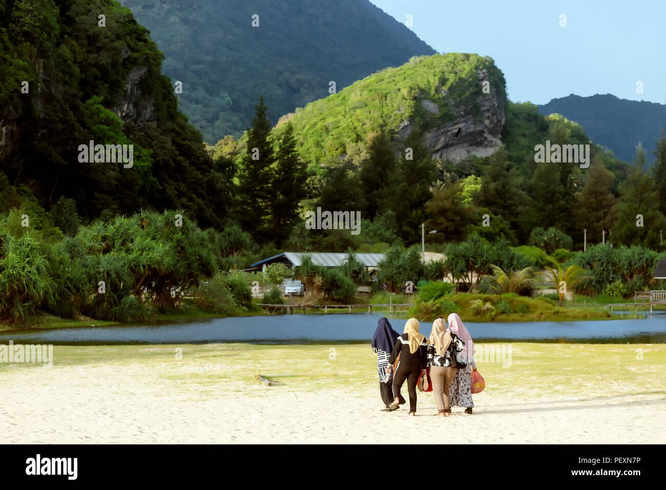 Women in hijabs walking on lakeshore, Banda Aceh, Sumatra, Indonesia - Stock Image