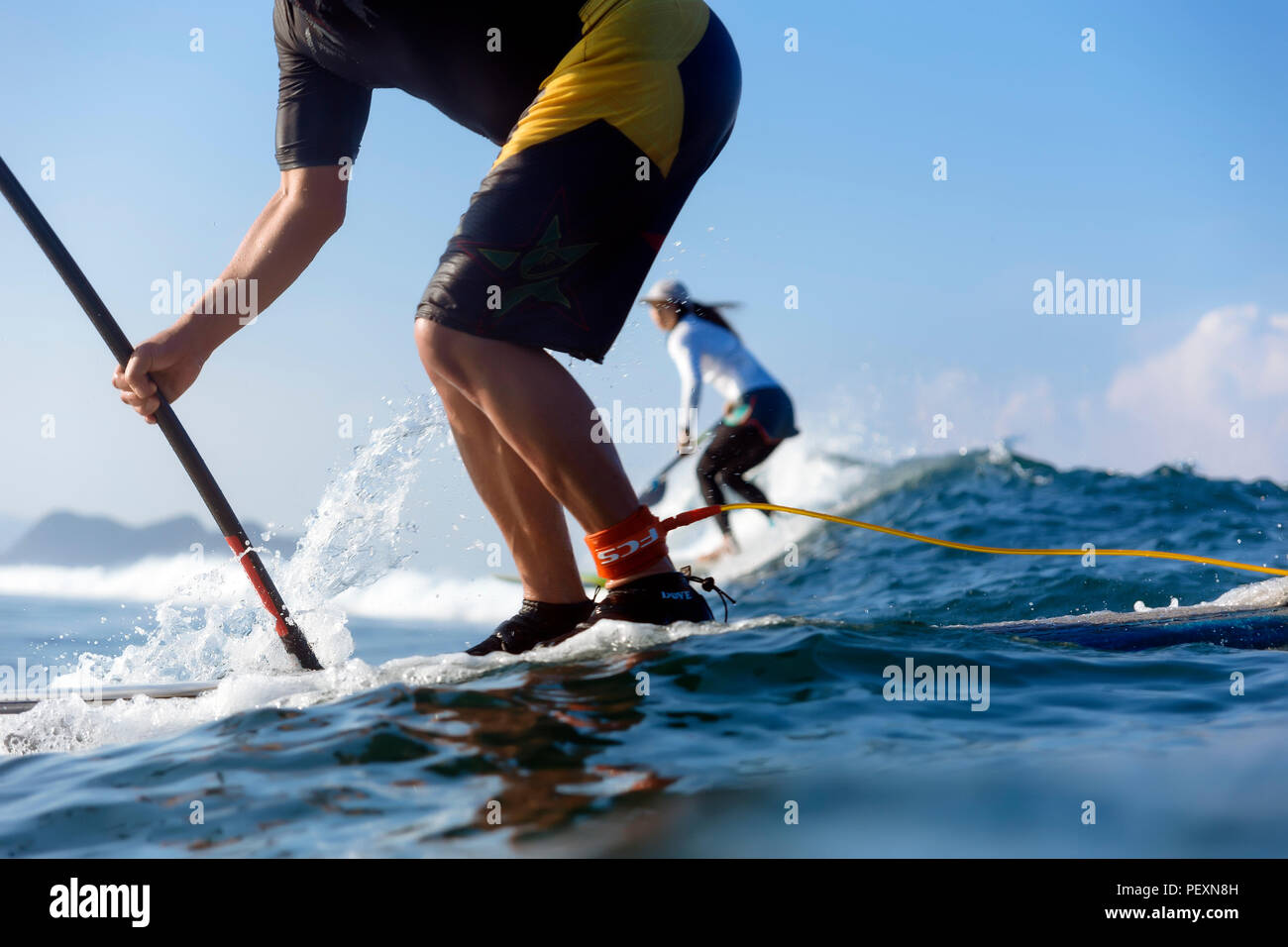 Two people paddle surfing in sea - Stock Image