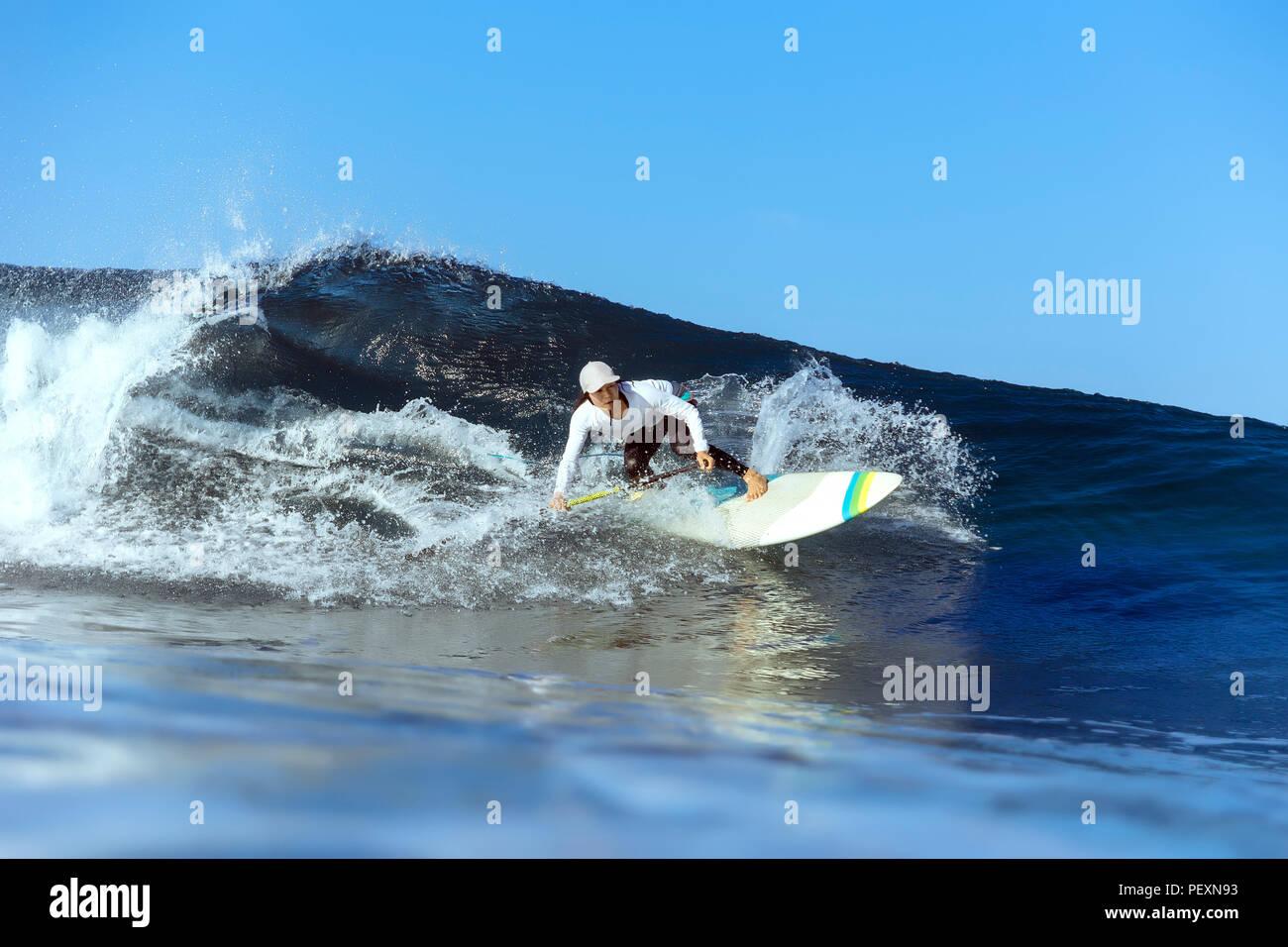 Female surfer riding wave - Stock Image