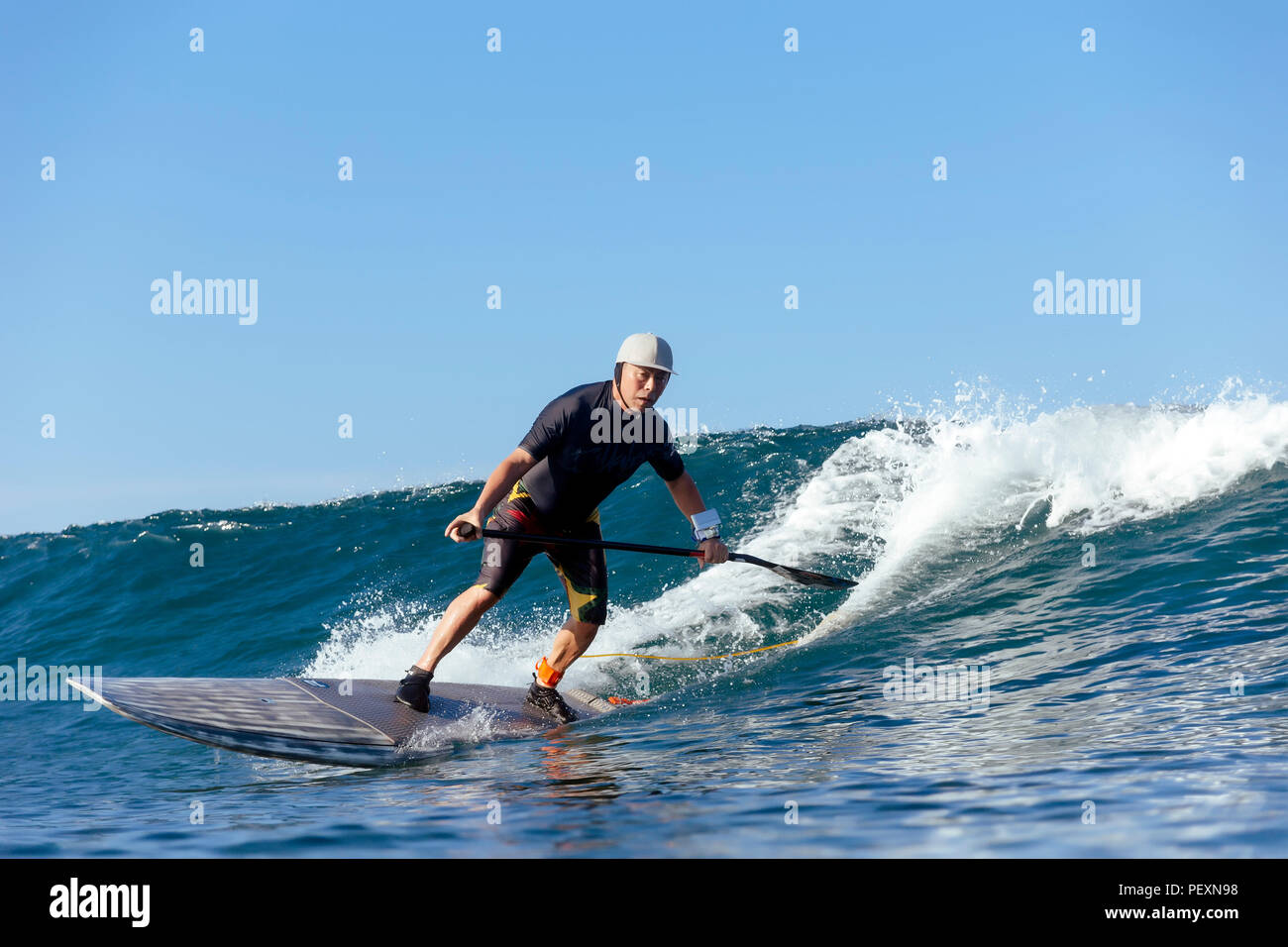 Paddle surfer riding wave - Stock Image