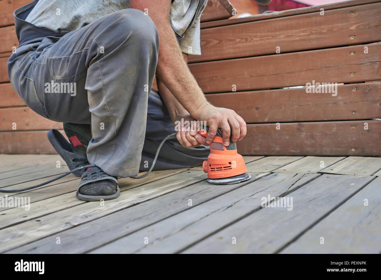 man grinds the parquet Stock Photo