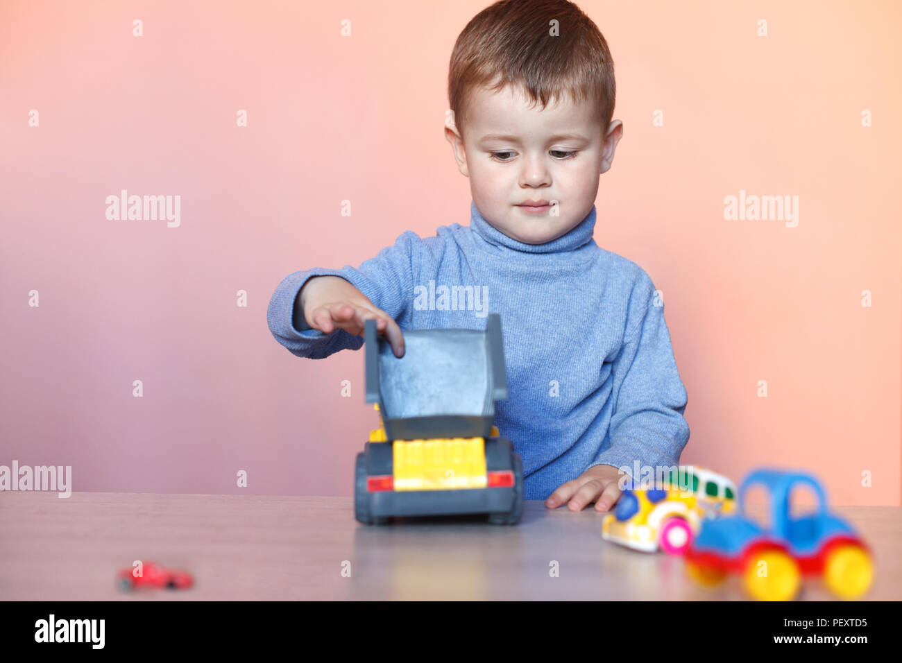 A cute little boy playing with model car collection. Toy mess in child room. - Stock Image