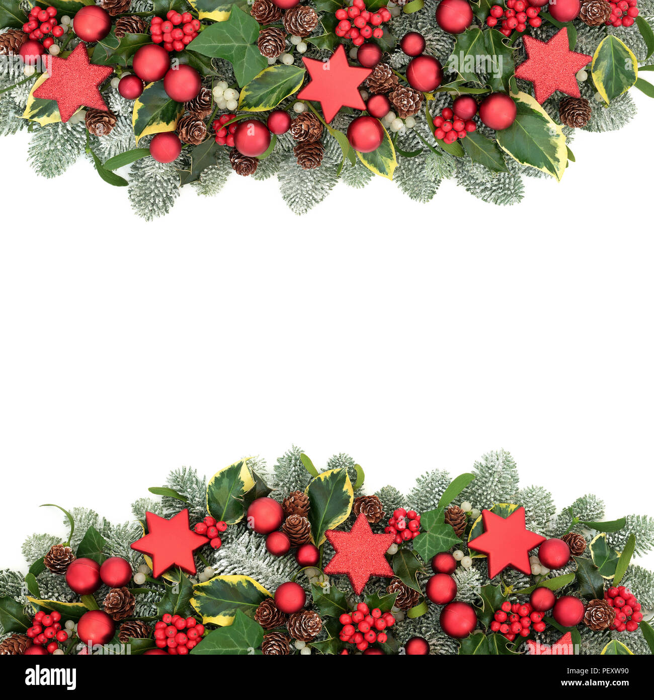 christmas festive background border with red bauble decorations winter flora of holly berries snow covered spruce pine ivy pine cones and mistleto