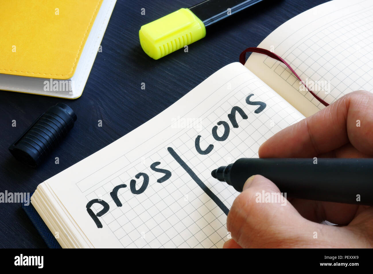 Man is writing list of pros and cons. - Stock Image