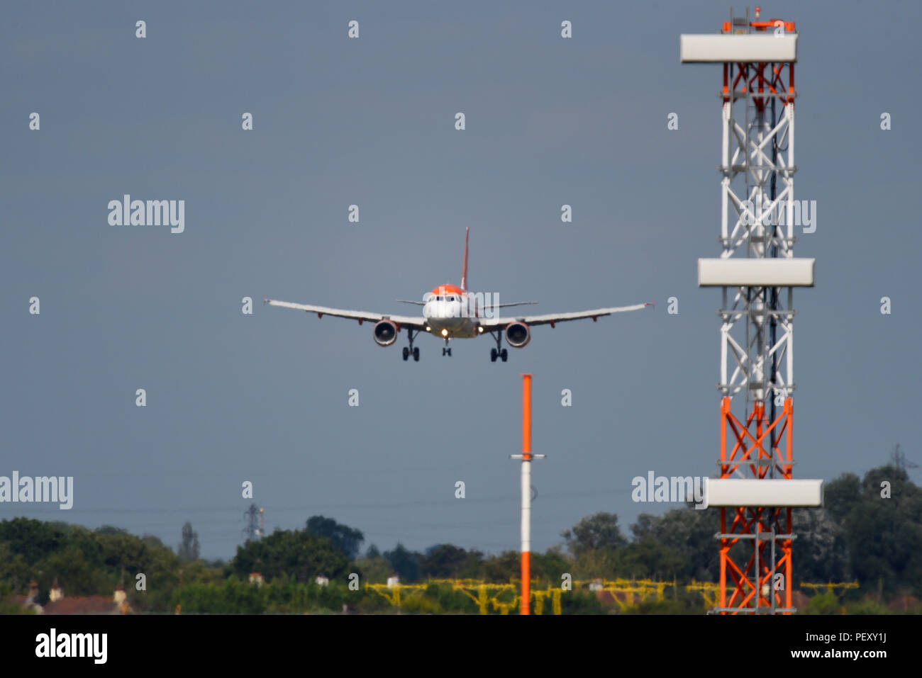 easyJet Airbus landing at London Southend Airport with ILS Glide slope tower landing system masts. Instrument Landing System infrastructure - Stock Image