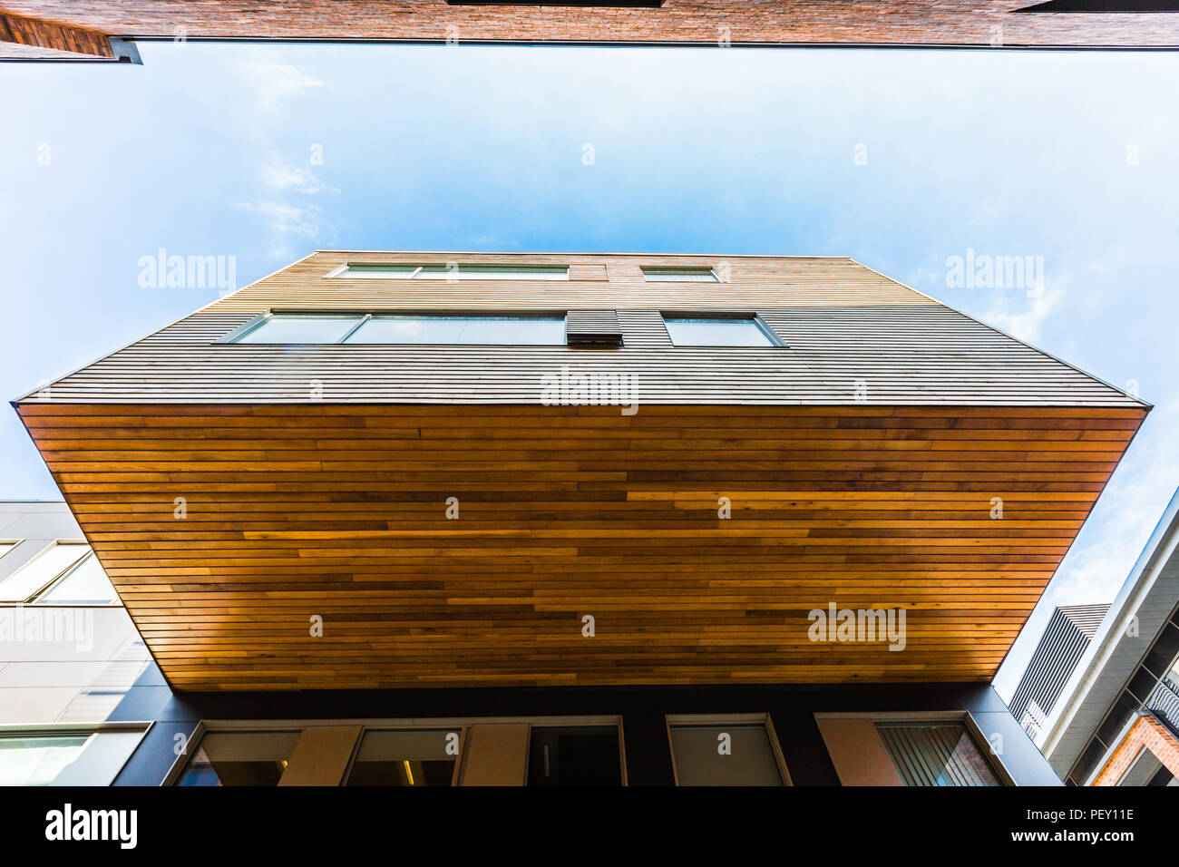 An example of a cantilever architecture with an external floating room on the side of a multi story building with wooden floor and walls - Stock Image