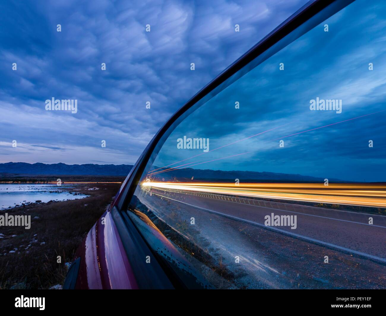 Cars vehicles trails trailing lights reflected off side window in dusk - Stock Image