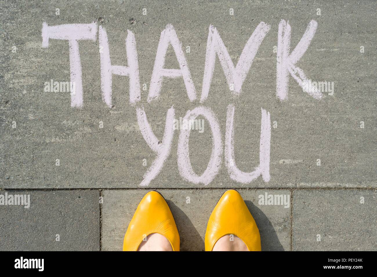 Female feet with text thank you written on grey sidewalk. - Stock Image