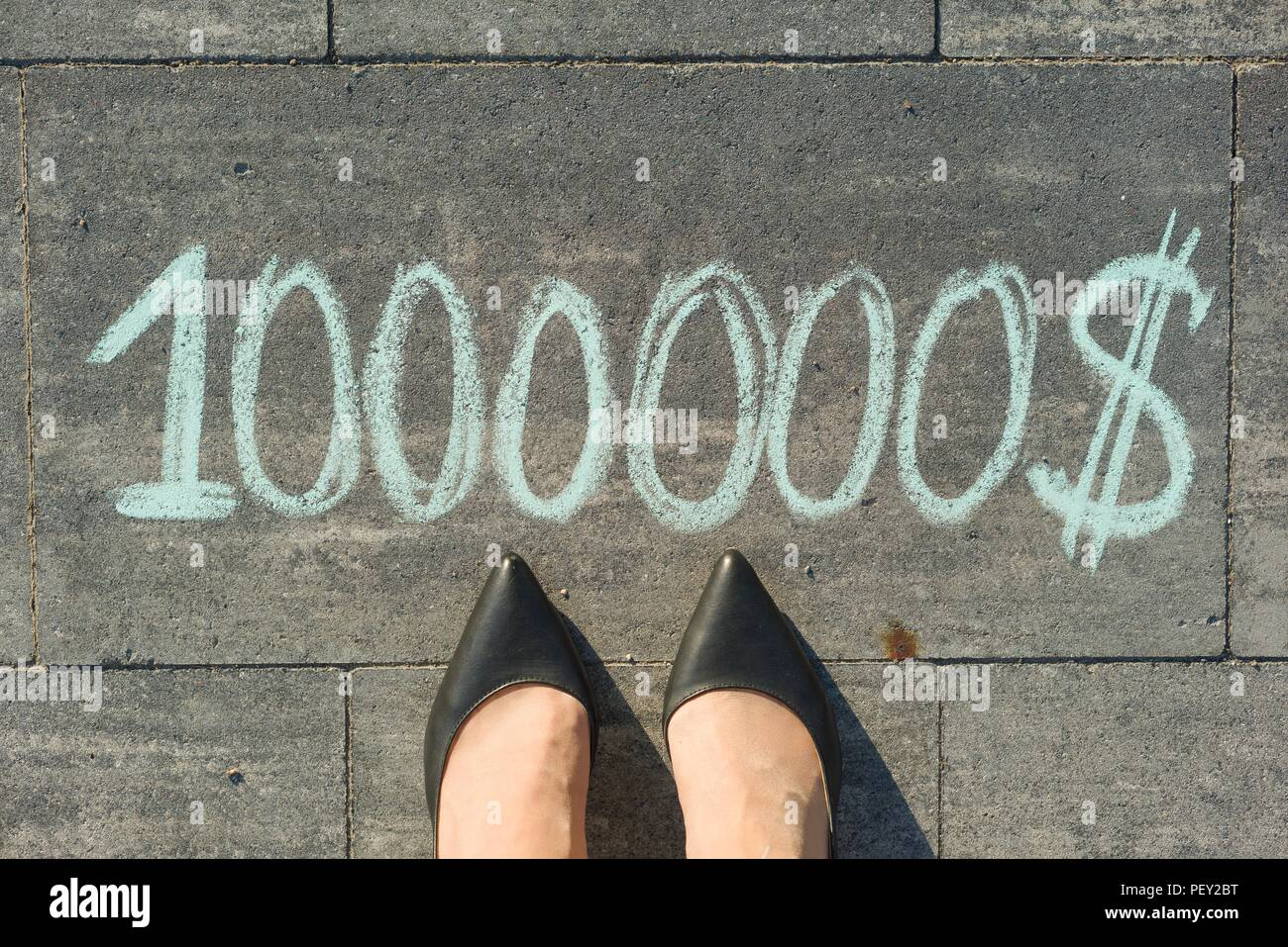 View from above, female feet with text 1000000 dollar written on grey sidewalk - Stock Image