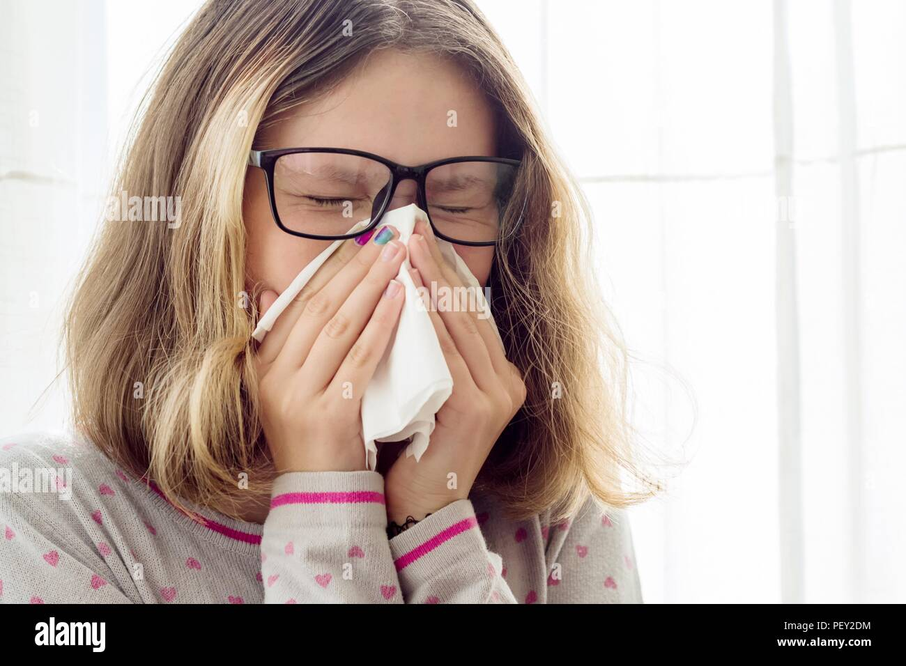 Sick teen girl with handkerchief at the home - Stock Image
