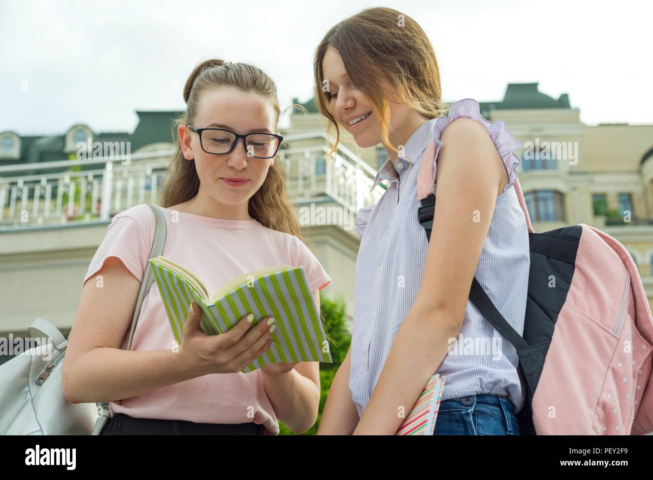 Portrait of two schoolgirls of teenagers with school backpacks and books. - Stock Image