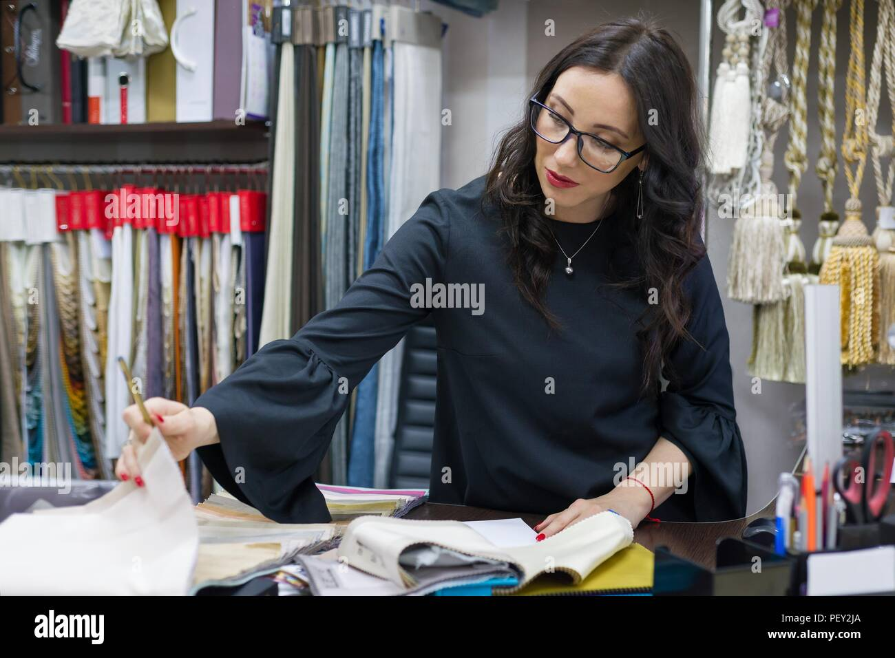 Woman owns a store of interior fabrics and decor works with samples of materials. Small business home textile shop - Stock Image