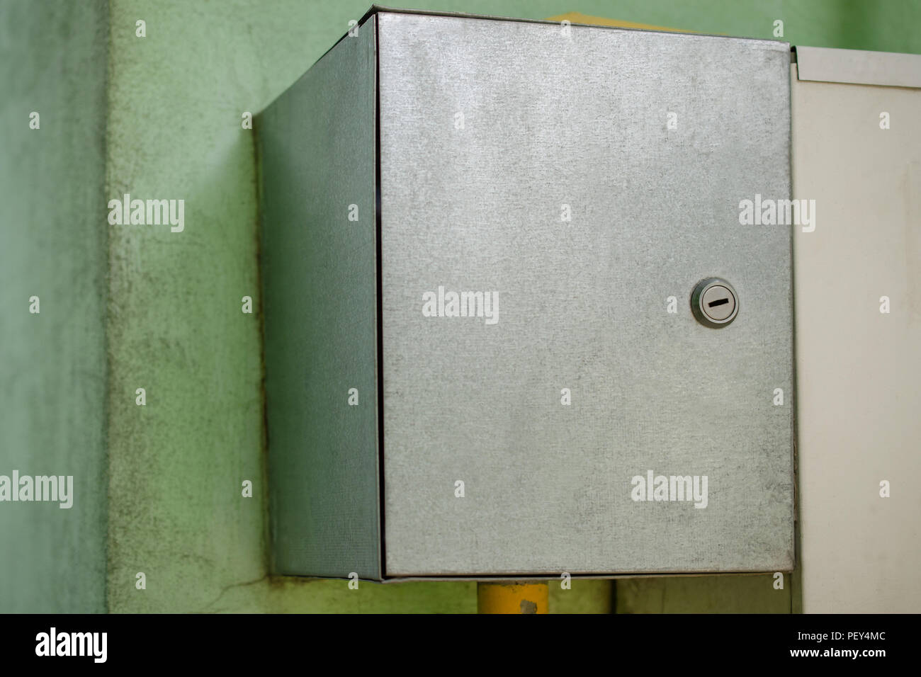 Gray electric or gas switch box, hanging on the wall. Equipment of a private house. Outdoors. Close-up. Stock Photo