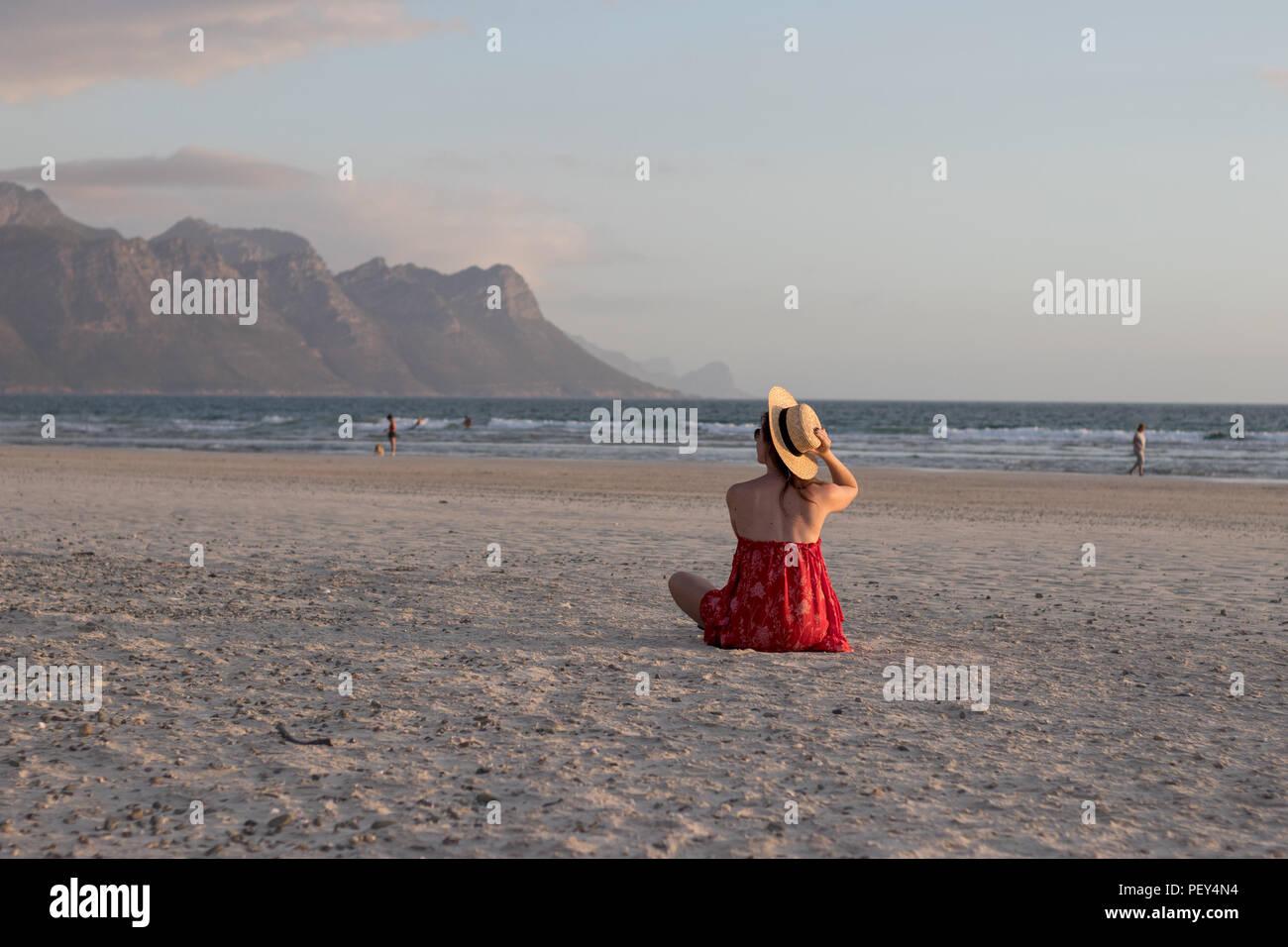 girl with red dress at beach sitting with sun hat, frau sitzt am strand mit rotem kleid und sonnehut, bergkulisse, mountain viw, pastell - Stock Image