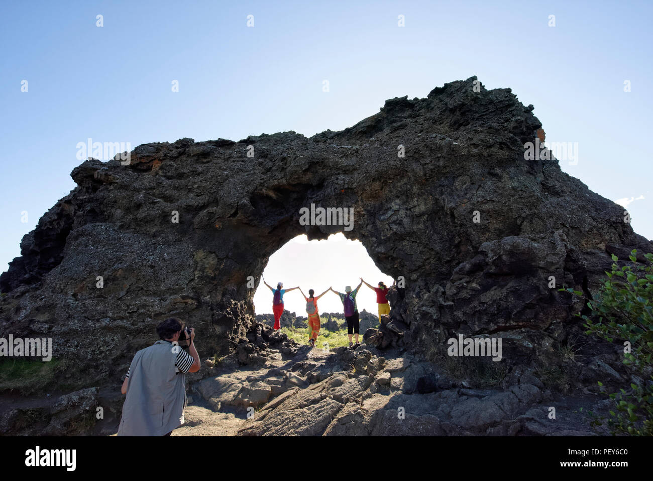 Woman standing in a natural Rock arch, lava field, Krafla volcanic system, Dimmuborgir National Park, Myvatn, Iceland Stock Photo