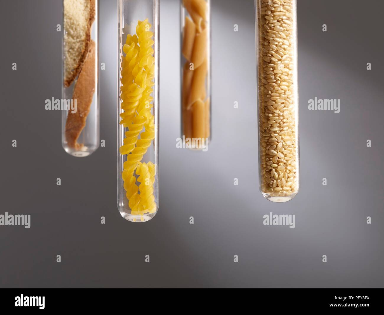 Carbohydrate foods in test tubes, studio shot. - Stock Image