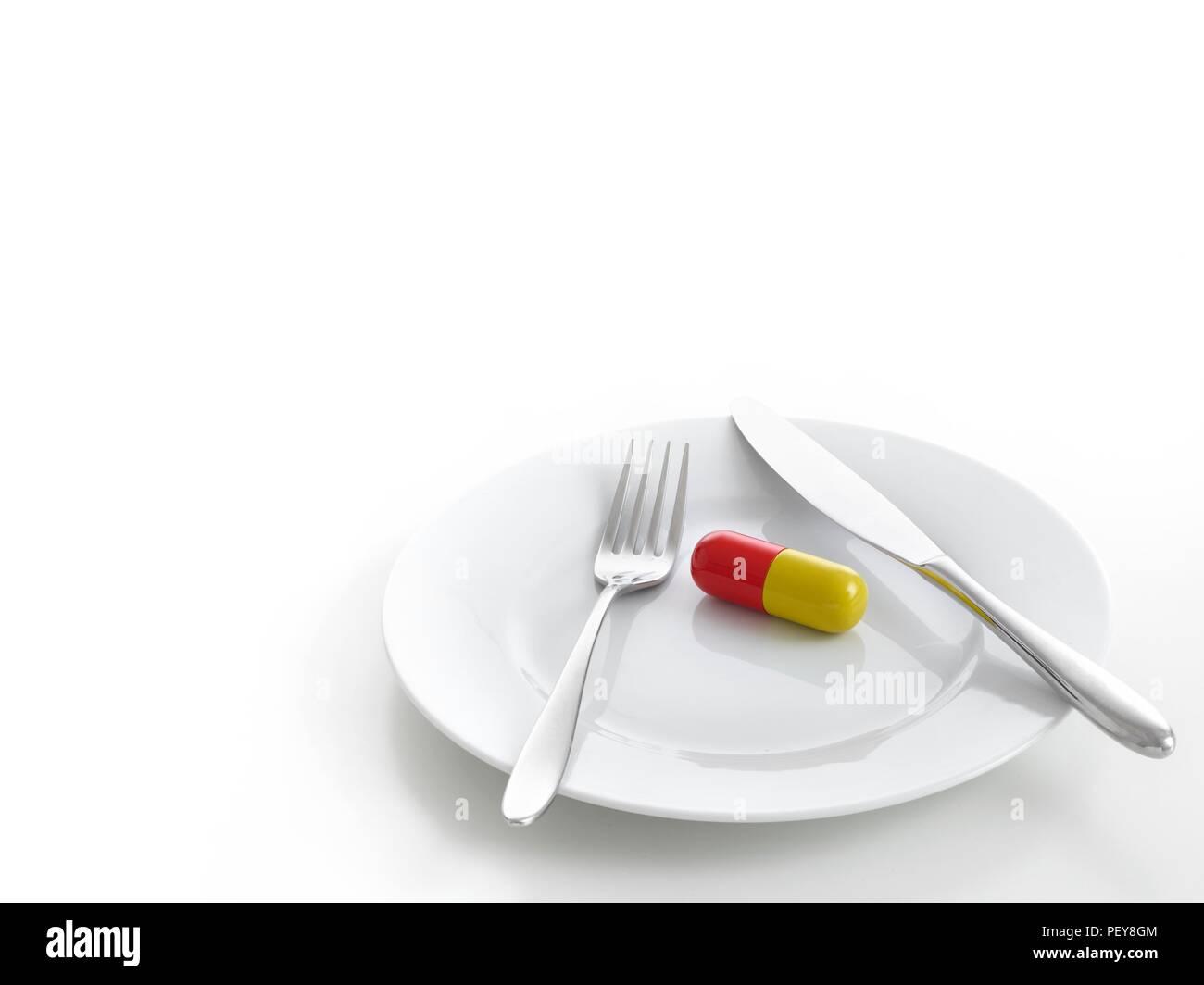 Capsule on dinner plate, studio shot. - Stock Image