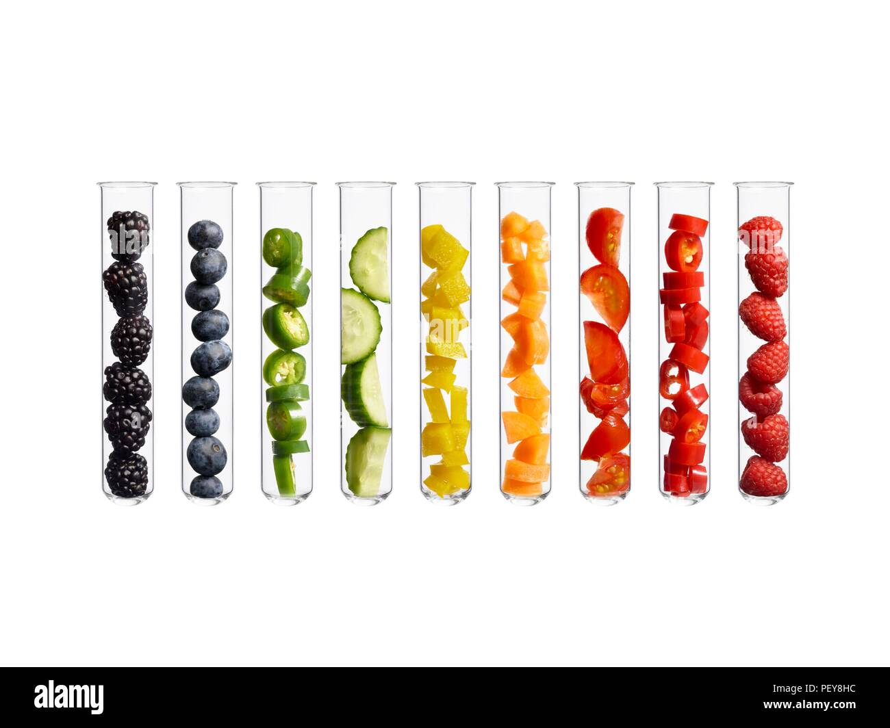 Fruits and vegetables in test tubes, studio shot. - Stock Image