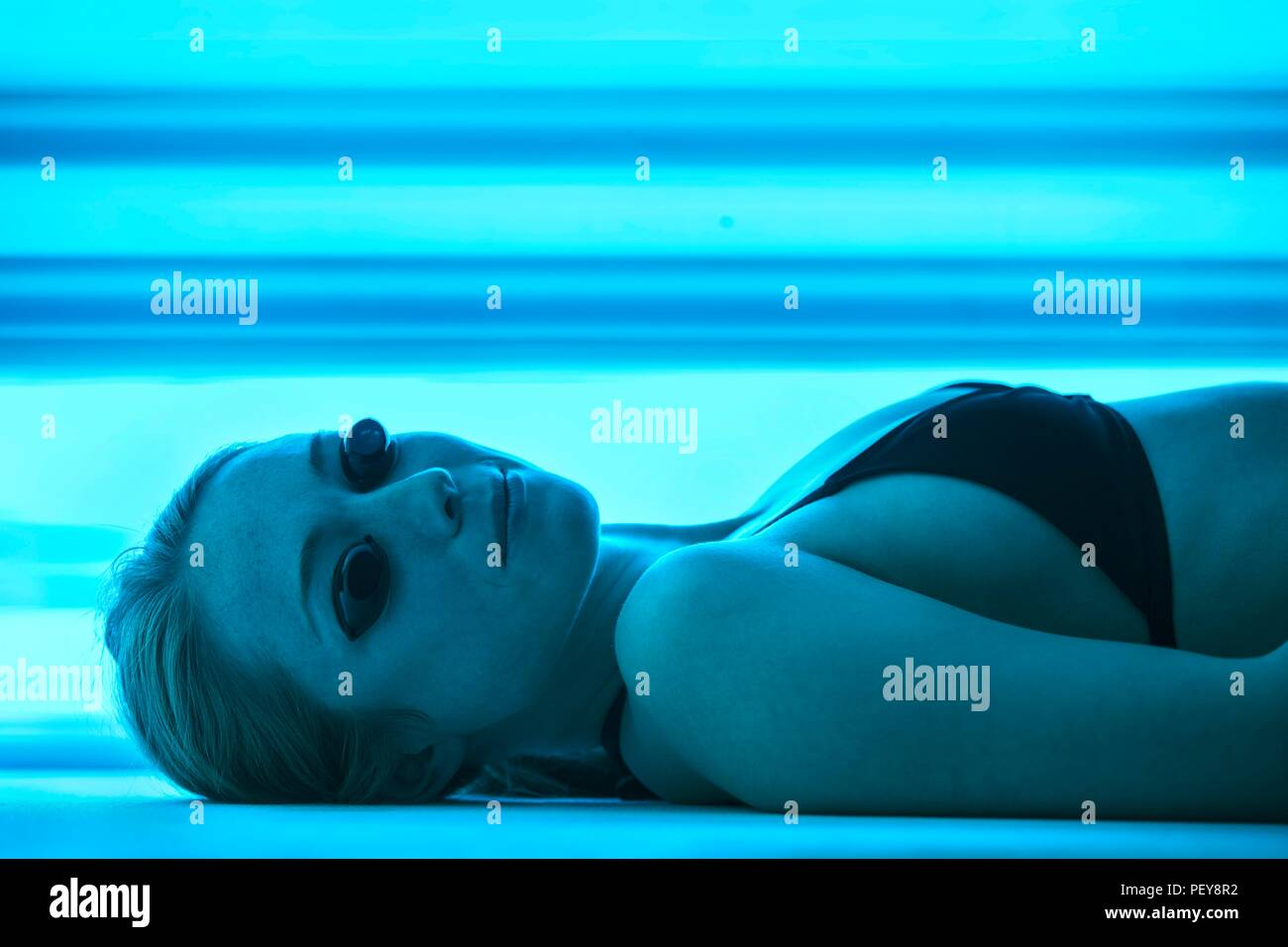 Woman wearing protective goggles in tanning booth. - Stock Image