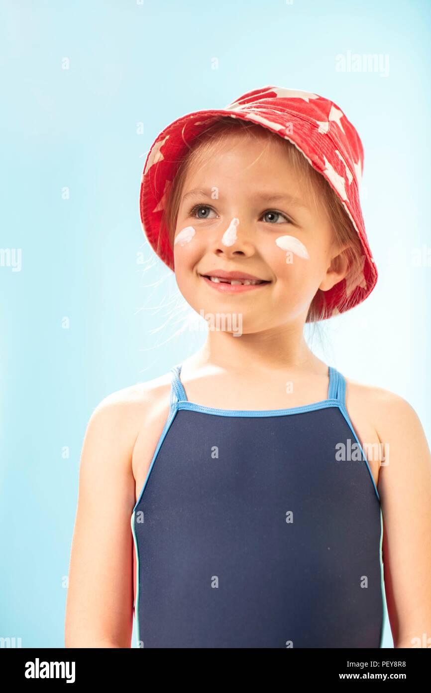 Girl wearing sunhat and suncream, portrait. - Stock Image