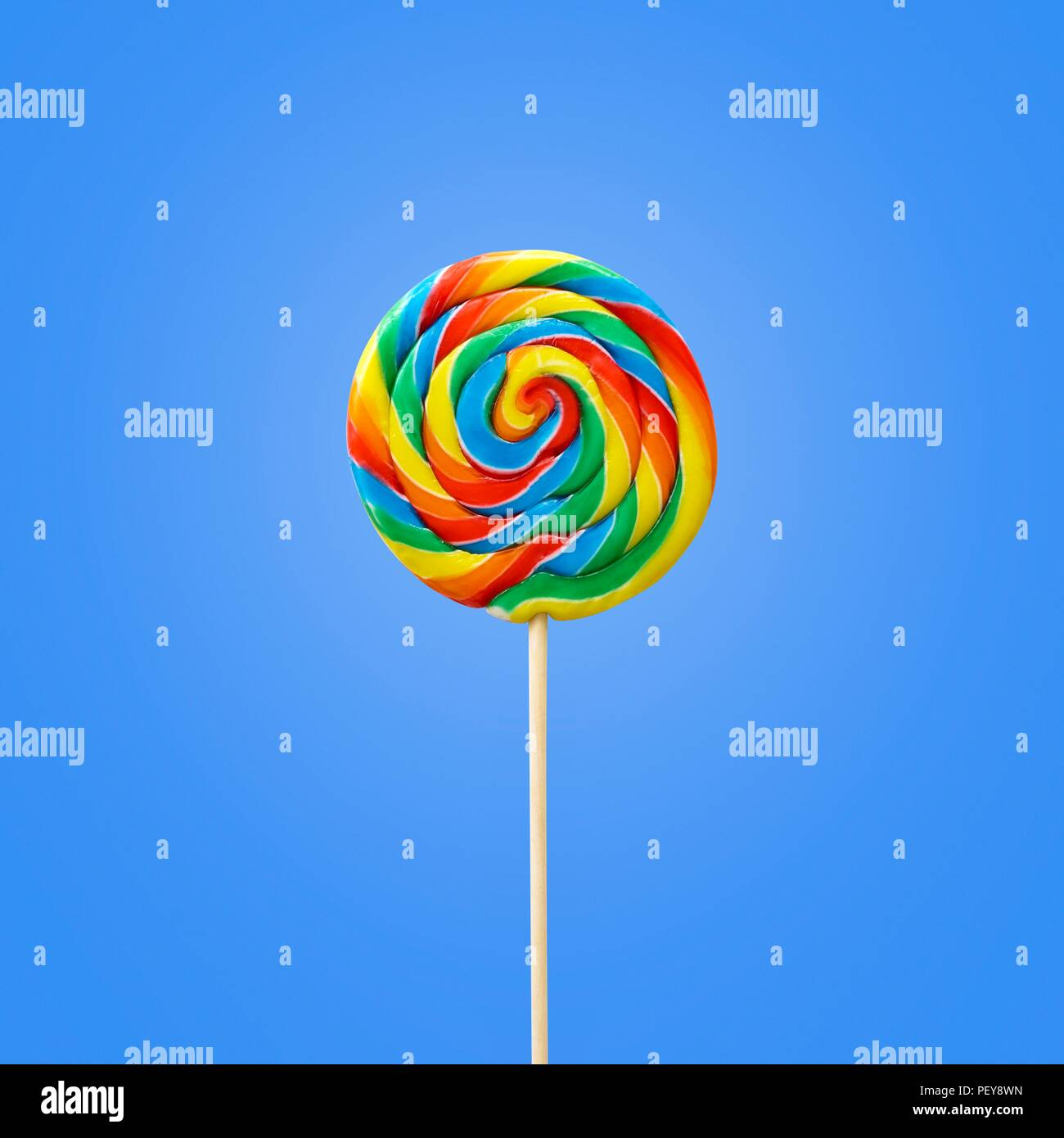 Bright coloured lollipop against a blue background. - Stock Image
