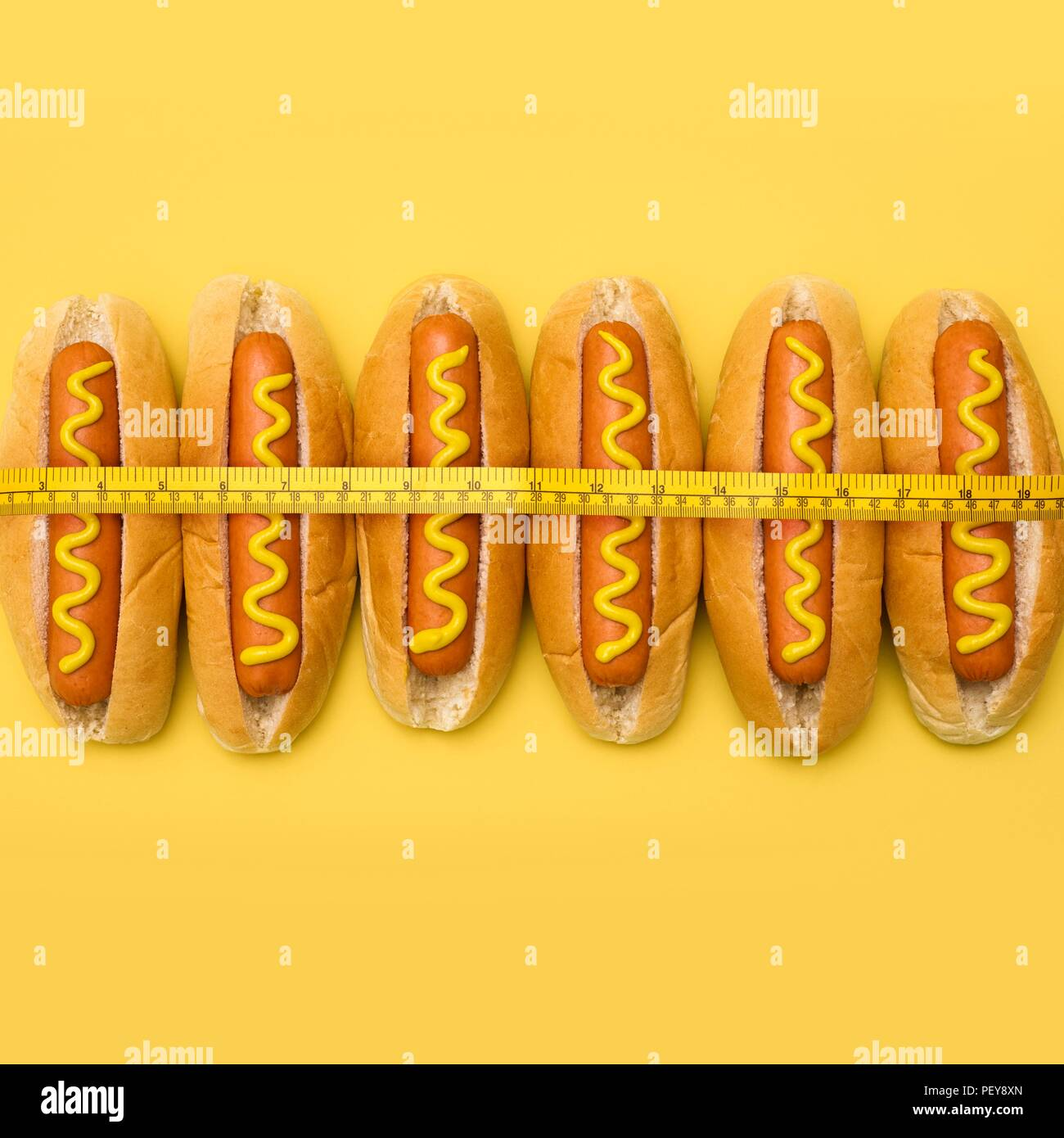 Dieting, conceptual image. Measuring tape around hot dogs. - Stock Image
